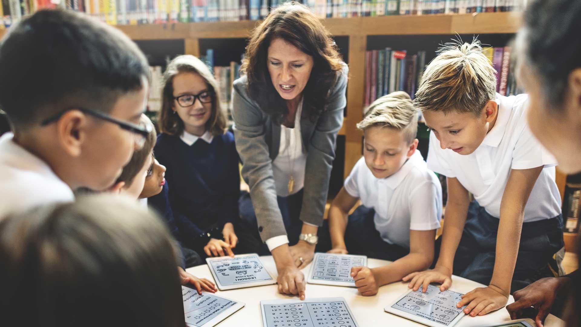 School-children-learning-skills-for-work-with-teacher-ipads.jpg